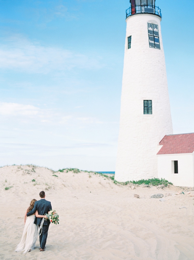 Bride and groom walk toward a lighthouse on a Nantucket beach