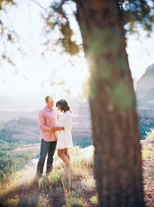 Engaged couple on a Sedona hilltop. Cotton lace dress for her, pink oxford shirt and jeans for him.