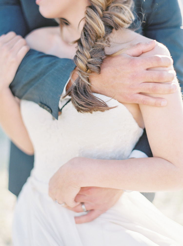 Bride with a fishtail braid embraced from behind