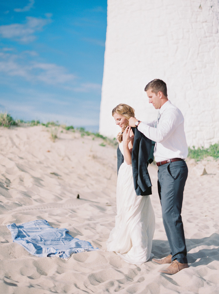 Groom offers his bride a jacket on a chilly beach