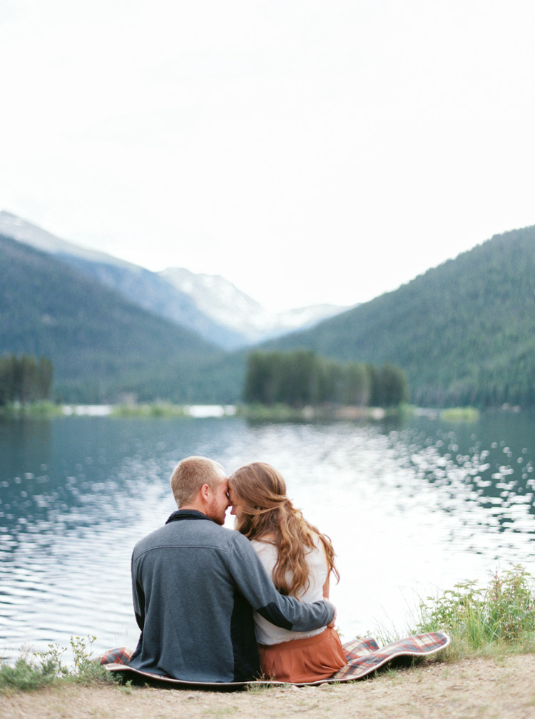 Nuzzling by a Colorado lake. Beautiful outdoor engagement shoot.