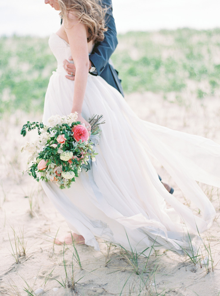 Bride with a lush pink bouquet walks on the beach with her groom