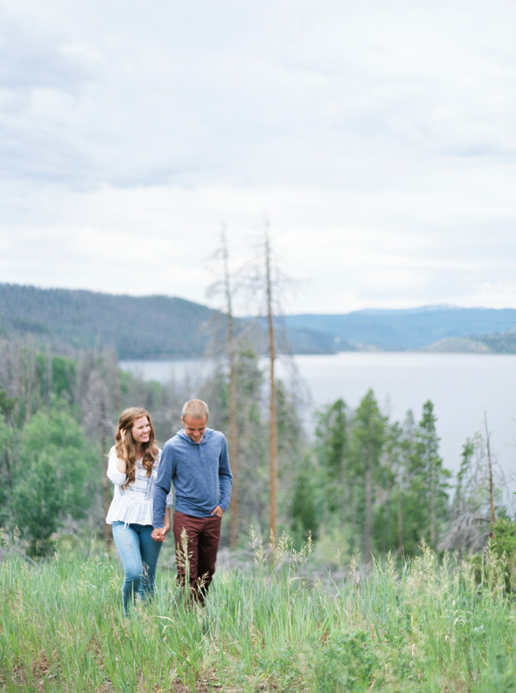 Engagement session strolling in outdoor meadow hand in hand in Colorado