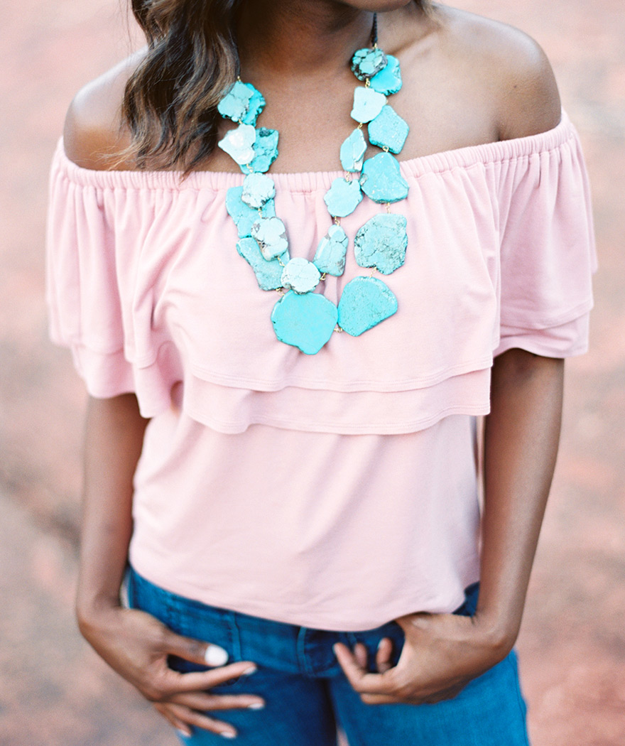Chunky turquoise necklace, pink off-shoulder top, and jeans. Flattering outfit for everyone!