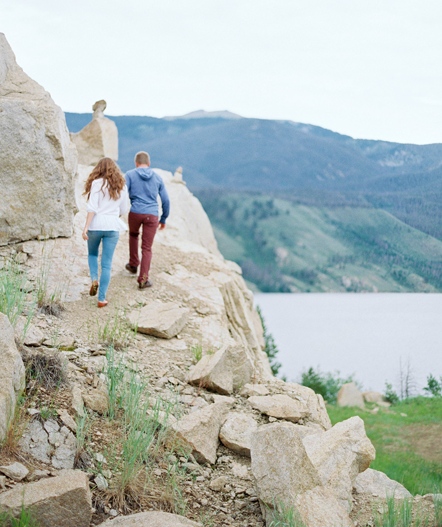 Engaged couple hiking mountainside in Rocky, Colorado shoot