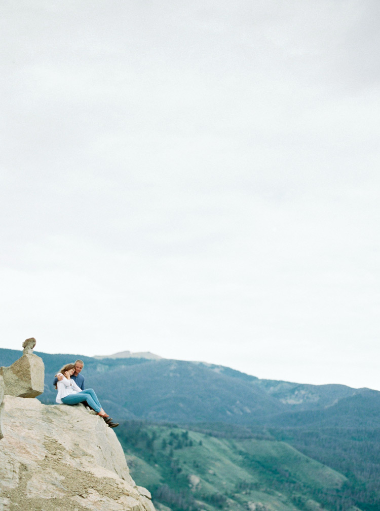 Couple sitting cliffside in Colorado mountains photo shoot