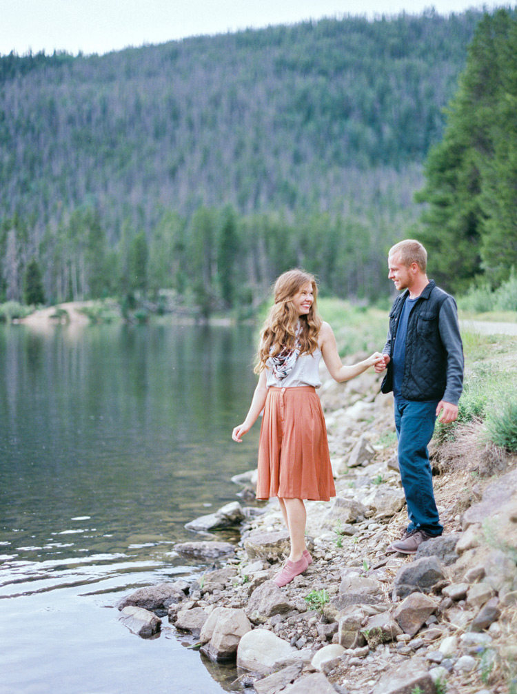 Bride looks back at fiancé near lake in Colorado