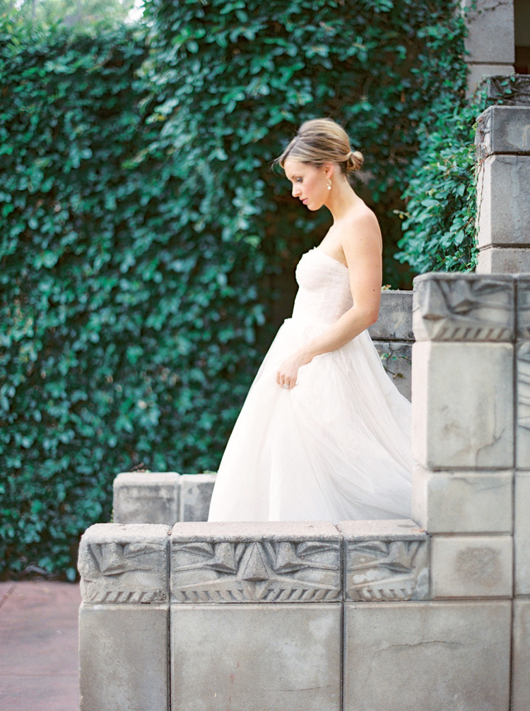 Bride in a strapless gown with a soft tulle skirt descends the steps at the Arizona Biltmore.