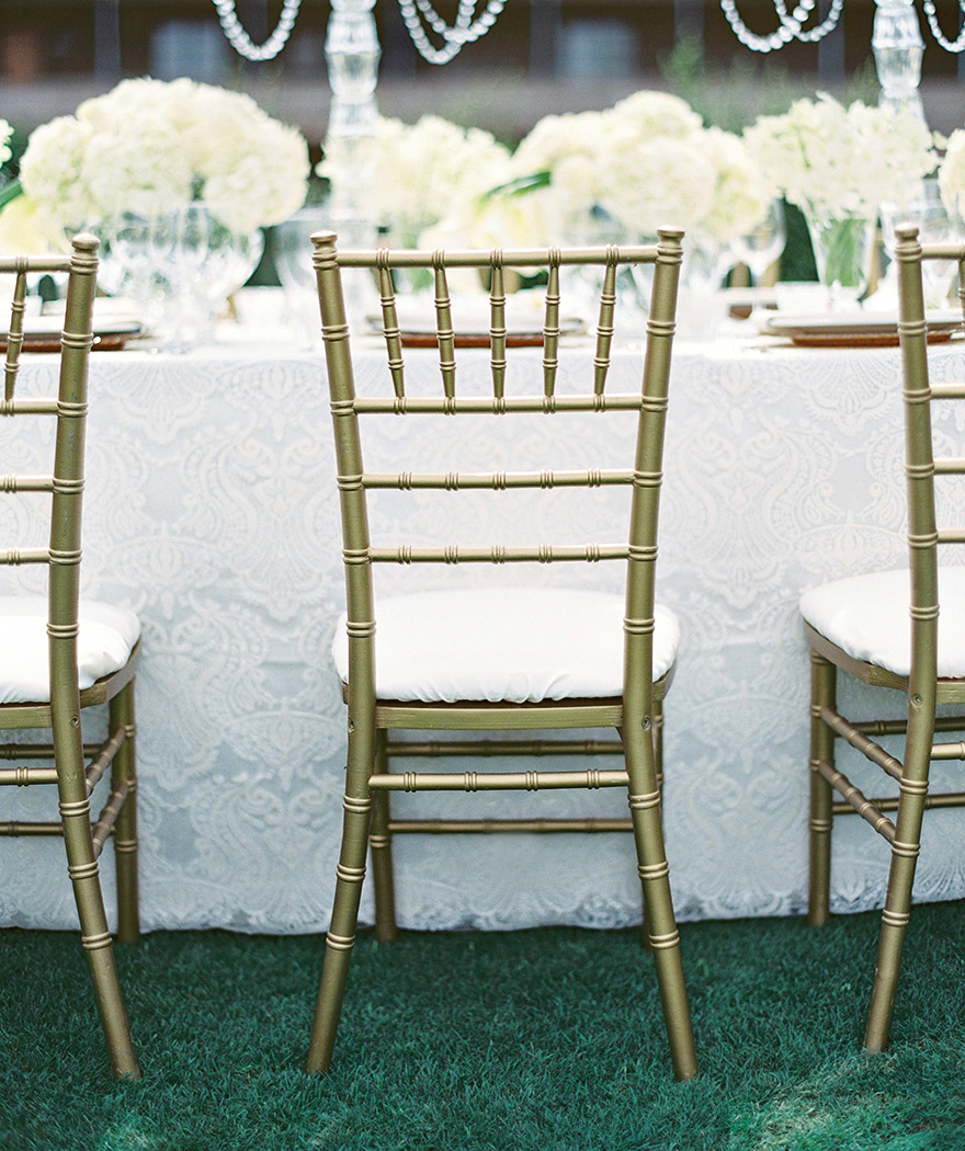 White and gold reception table for an elegant, monochrome wedding. Outdoor reception.