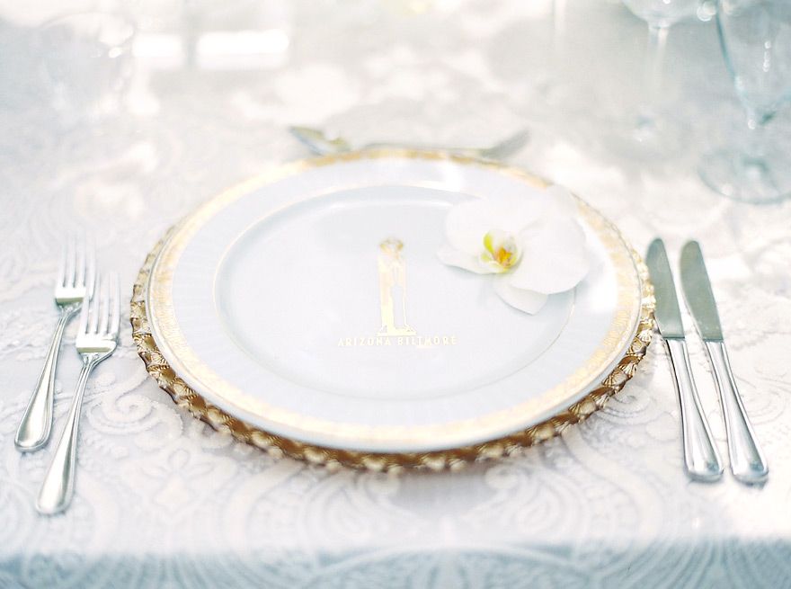 White lace linens set with white and gold plates. Clean & elegant monochrome wedding reception.
