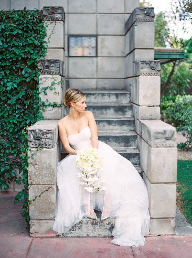 Bride in a strapless gown with a full skirt steals a quiet moment on the steps. All white bouquet.
