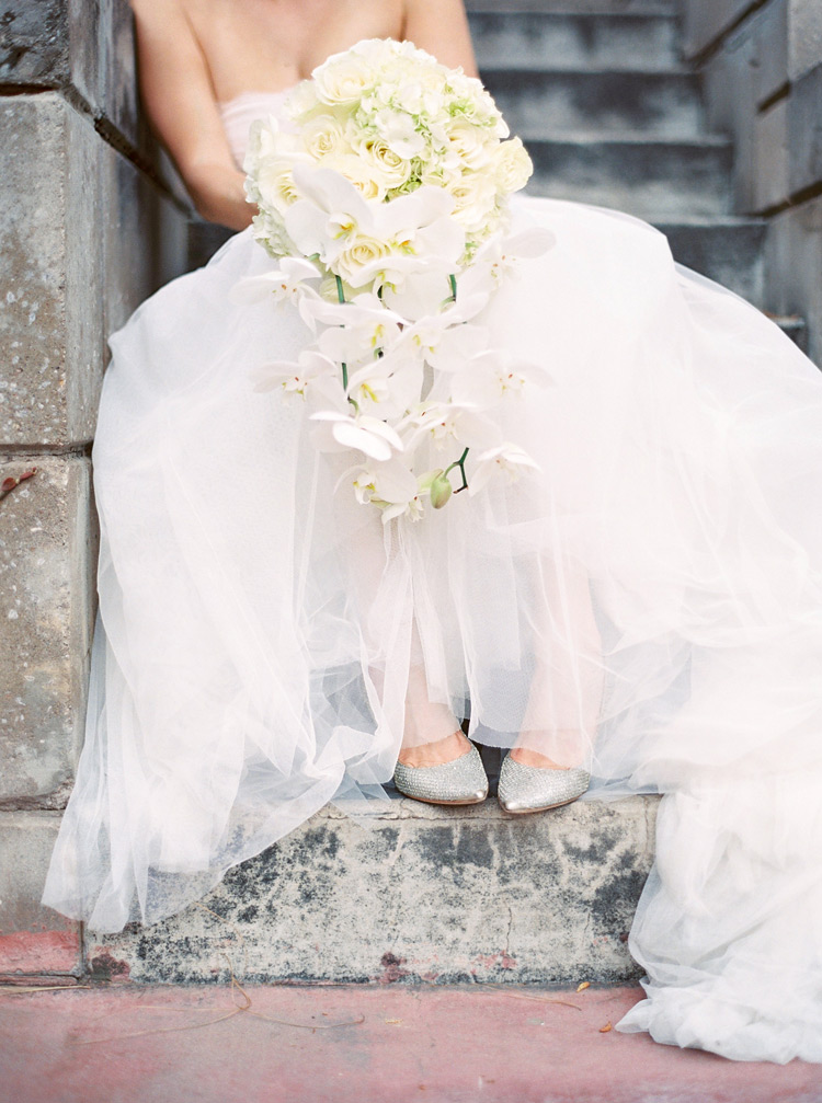 Wedding dress with a full tulle skirt, silver shoes, with an all white bouquet. Modern bride fashion