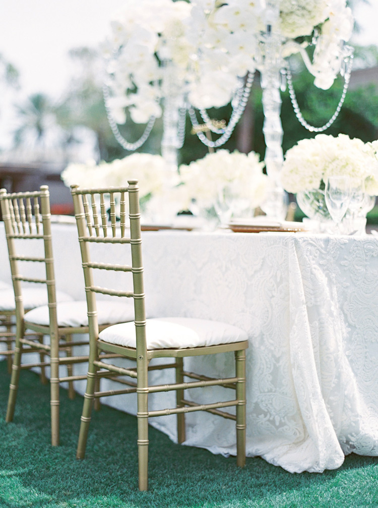 Reception table set with lush white flowers & white lace linens. Elegant monochrome wedding.