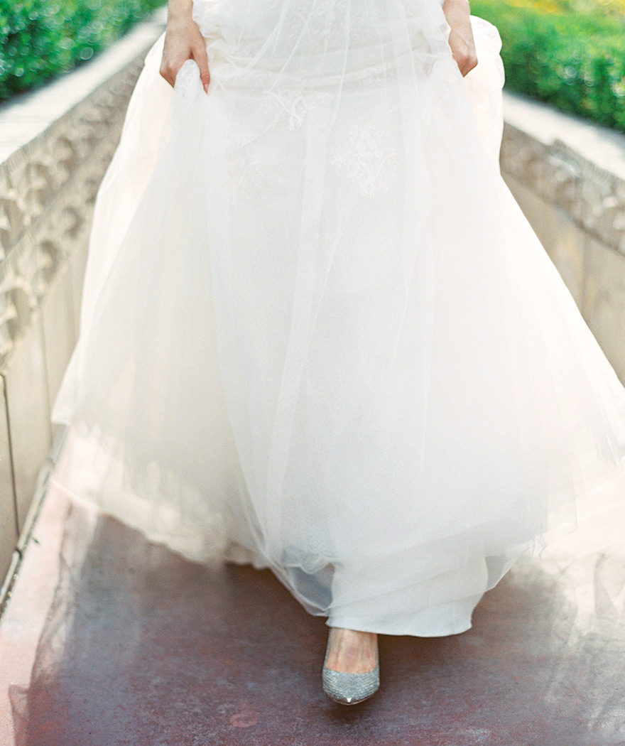 Full, lacey skirt of a beautiful wedding dress, lifted just above the bride's silver shoes.