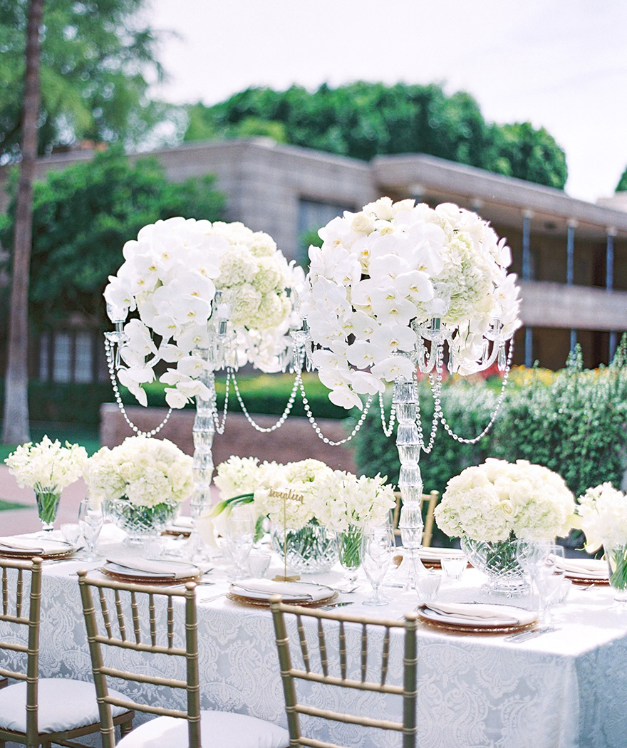 Outdoor reception table set with lush white flowers & white lace linens. Elegant monochrome wedding.