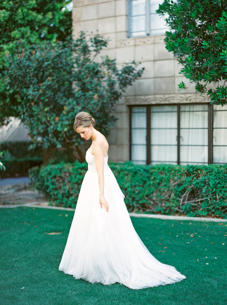 Bride in a strapless wedding dress enjoys the lawn at the Arizona Biltmore. Bridal portraits.