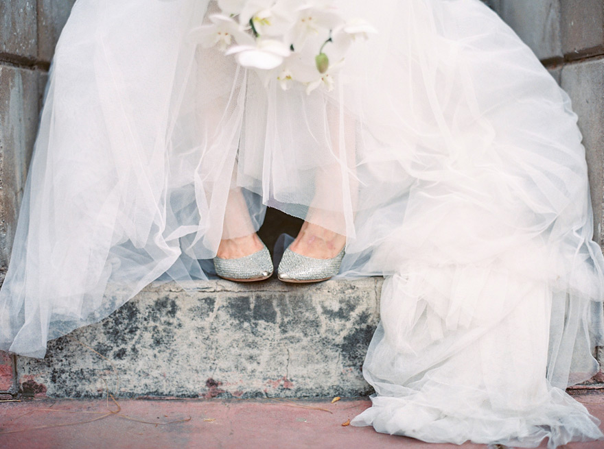 Silver wedding shoes peek out from beneath a full tulle skirt. Interesting bridal portraits.