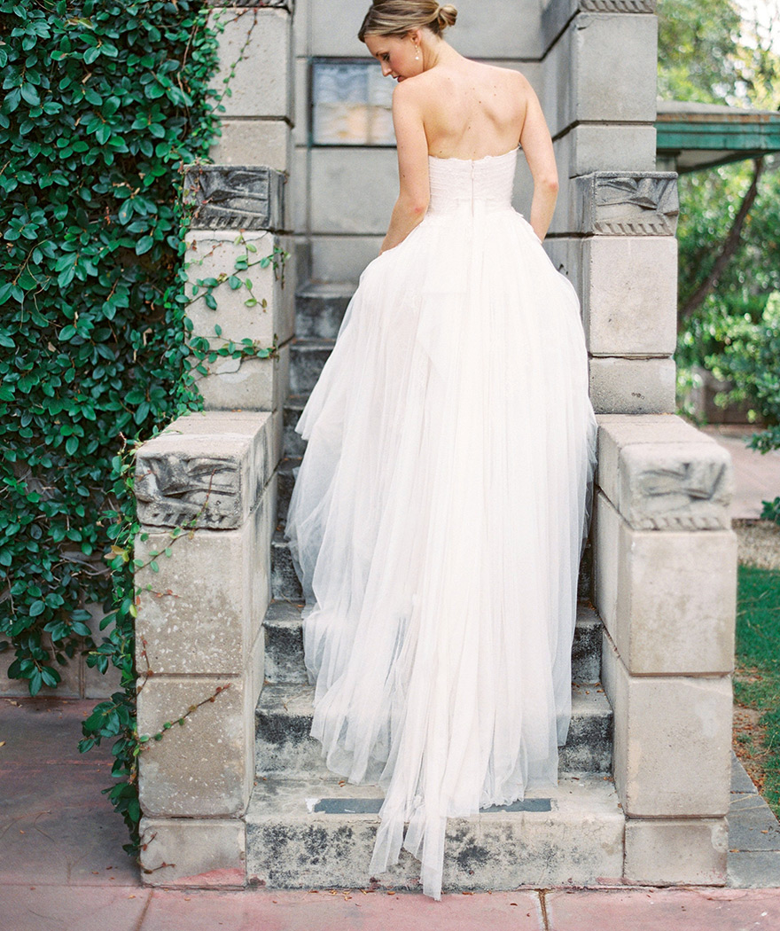 Back view of a bride in a gorgeous lace and tulle dress with a full skirt. Simple elegance.