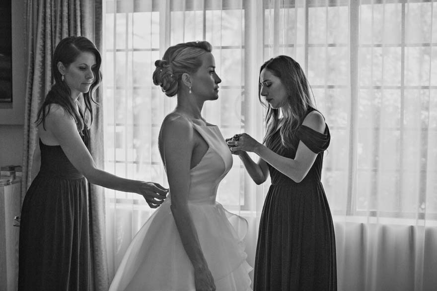bride assisted into her dress by her bridesmaids