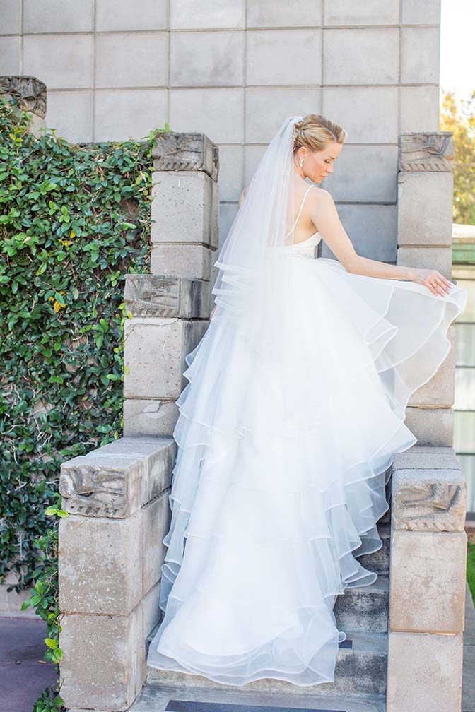 bride in a layered ballgown ascends the stairs