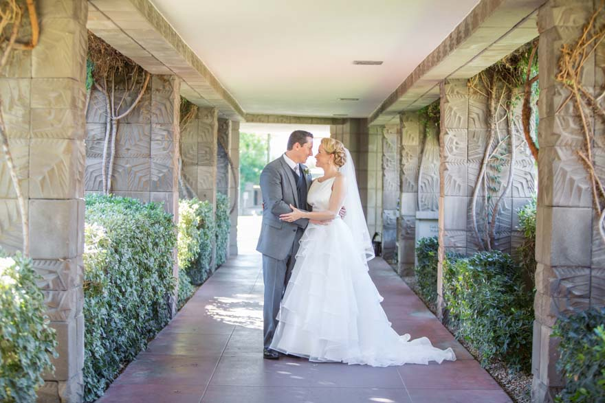 bride & groom surrounded by textured columns of the Arizona Biltmore