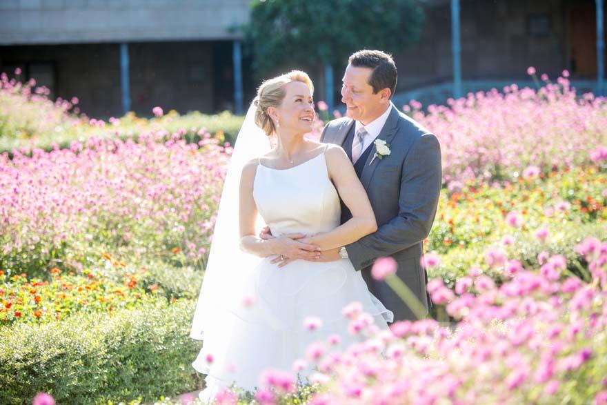 bride & groom embrace amidst pink flowers