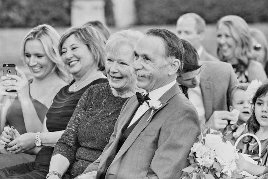 bride's happy parents watch the wedding ceremony
