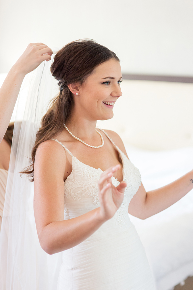 bride putting on her veil for her wedding