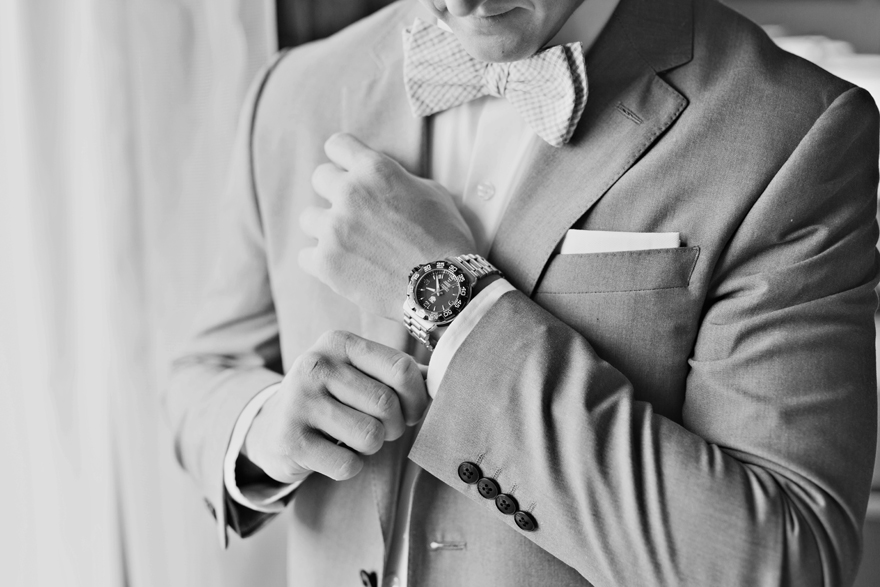 dapper groom finishes getting ready for his wedding