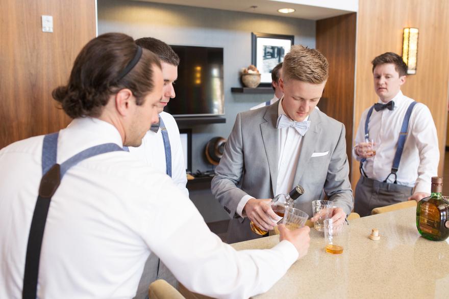 dapper groom pouring drinks for the groomsmen