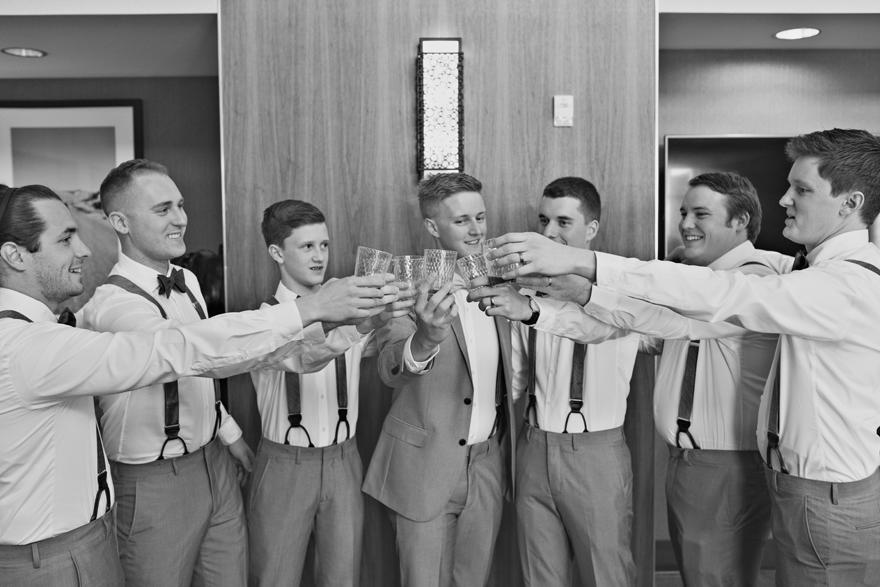groomsmen in suspenders toasting the groom