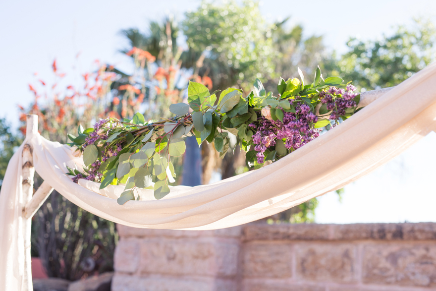 floral bower with draped fabric for an outdoor wedding ceremony