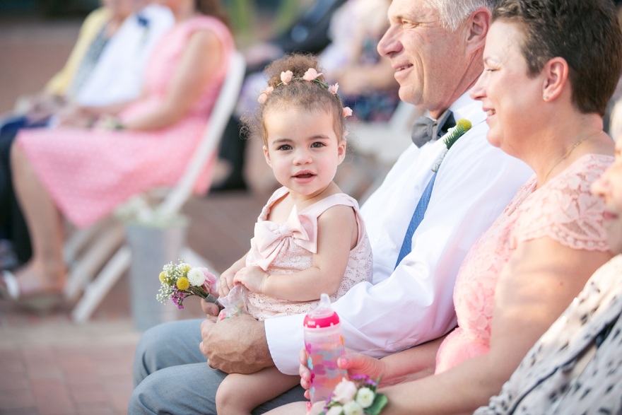 Toddler in blush holds a tiny bouquet and watches the wedding