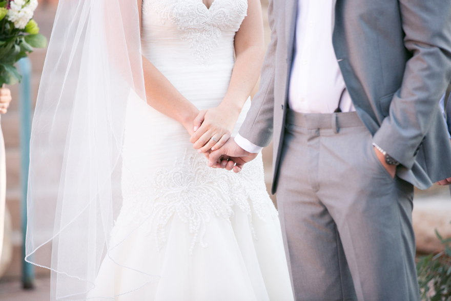 bride & groom hold hands during their outdoor wedding ceremony