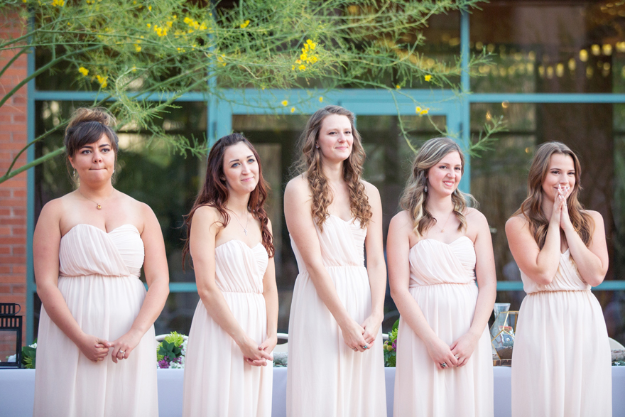 bridesmaids in blush watch the bride & groom's first dance