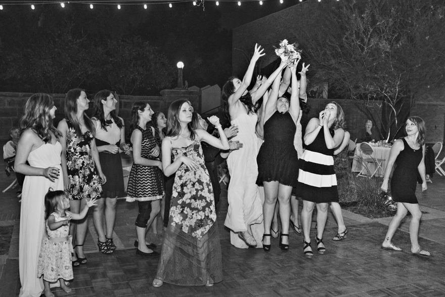 wedding guests leap to catch the bouquet
