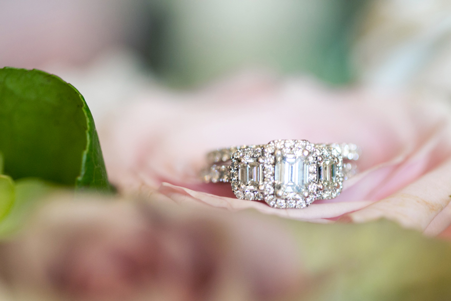 Elegant diamond engagement ring with 3 emerald cut diamonds surrounded by smaller stones.