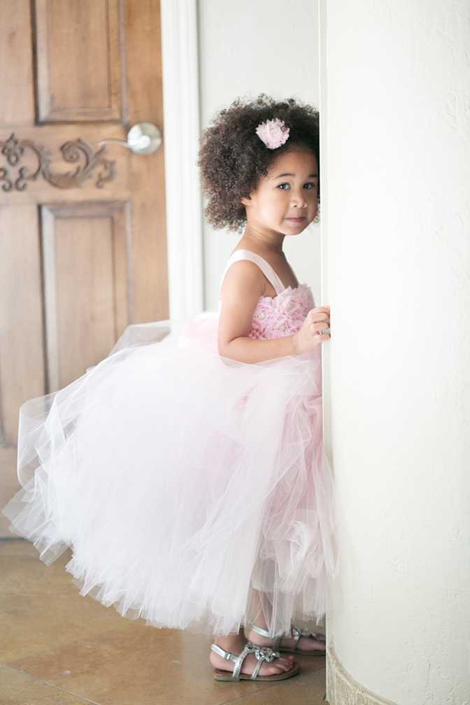 Adorable little girl wearing pink tulle and ruffles for a wedding