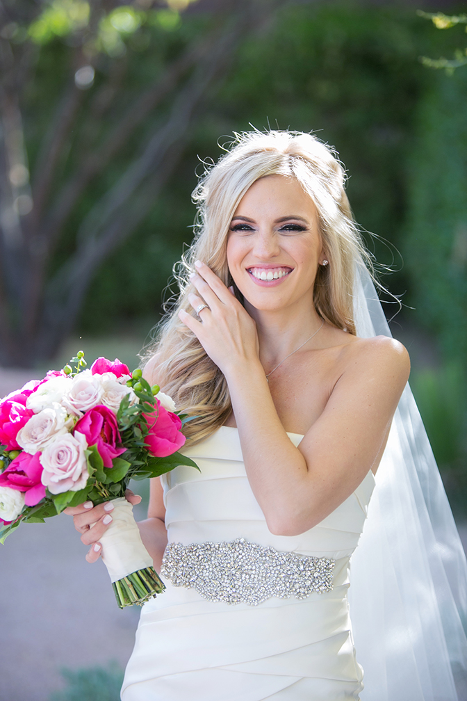 Smiling blonde bride holds a pink and fuchsia bouquet