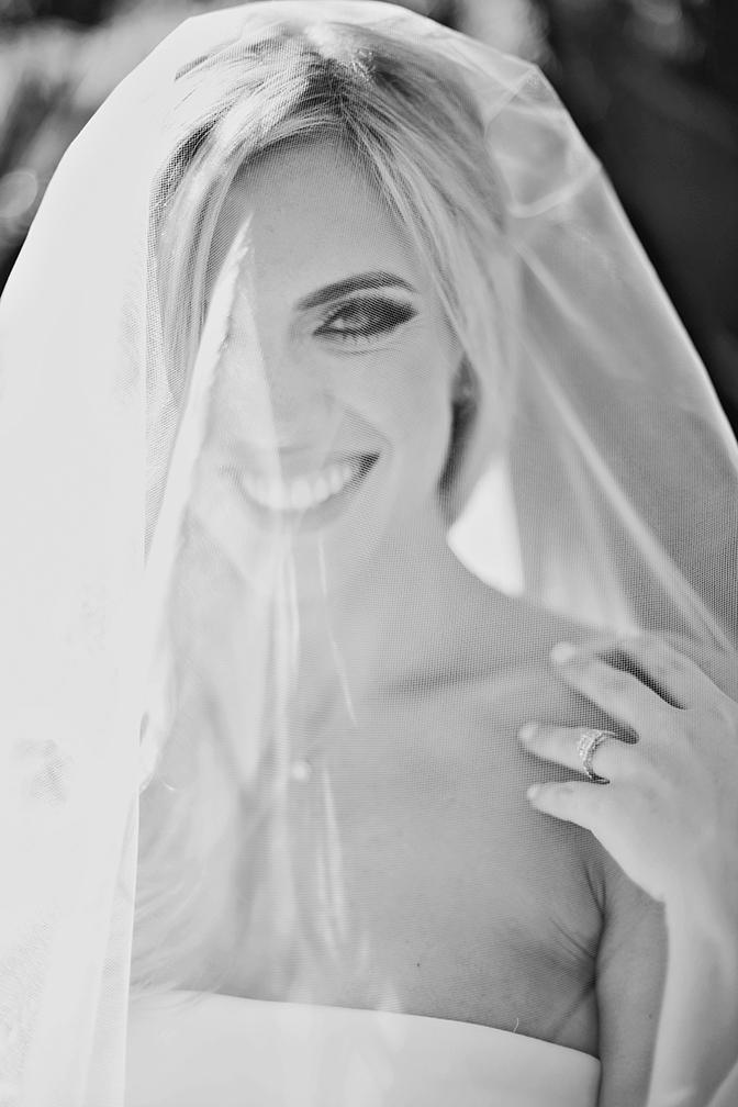 Veiled bride beams at the camera