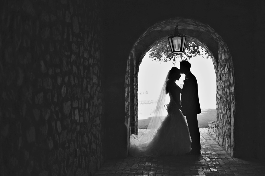 Silhouette of a bride & groom in a stone archway