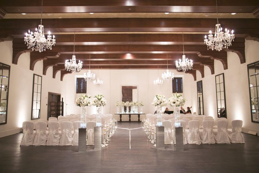 Elegant white wedding ceremony with chandeliers