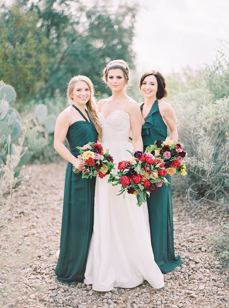elegant bride flanked by bridesmaids in emerald Amsale dresses