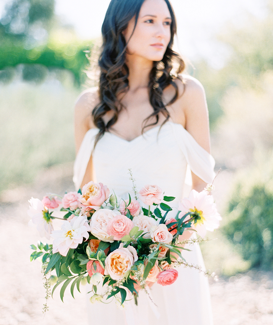 bride in an off-shoulder dress from Amsale with a soft coral bouquets