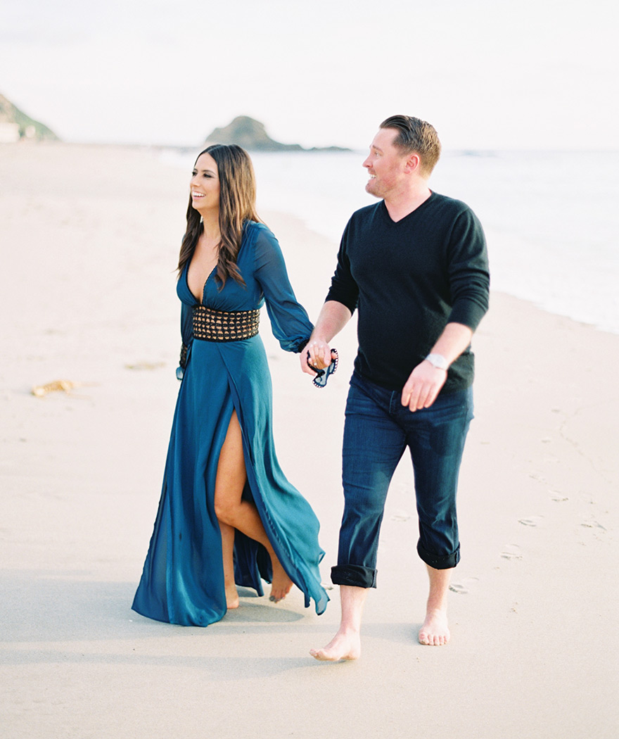 couple holding hands on Laguna beach, engagement session