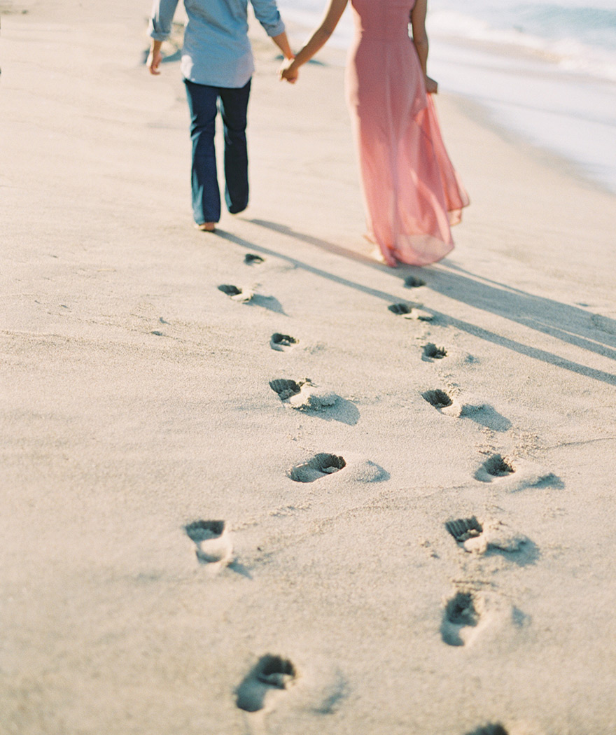 couple running on beach with footprints in the sand in Malibu, engagement session
