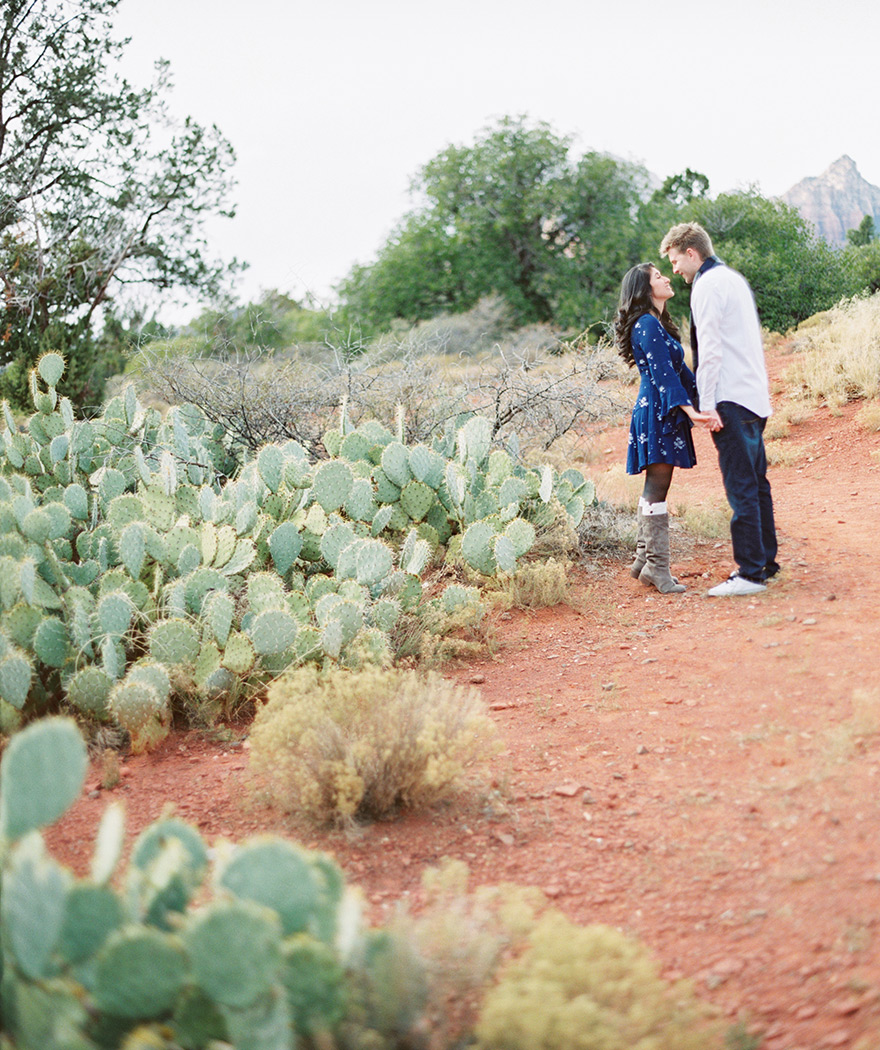 couple looking at each other with cacti and desert, Sedona engagement session