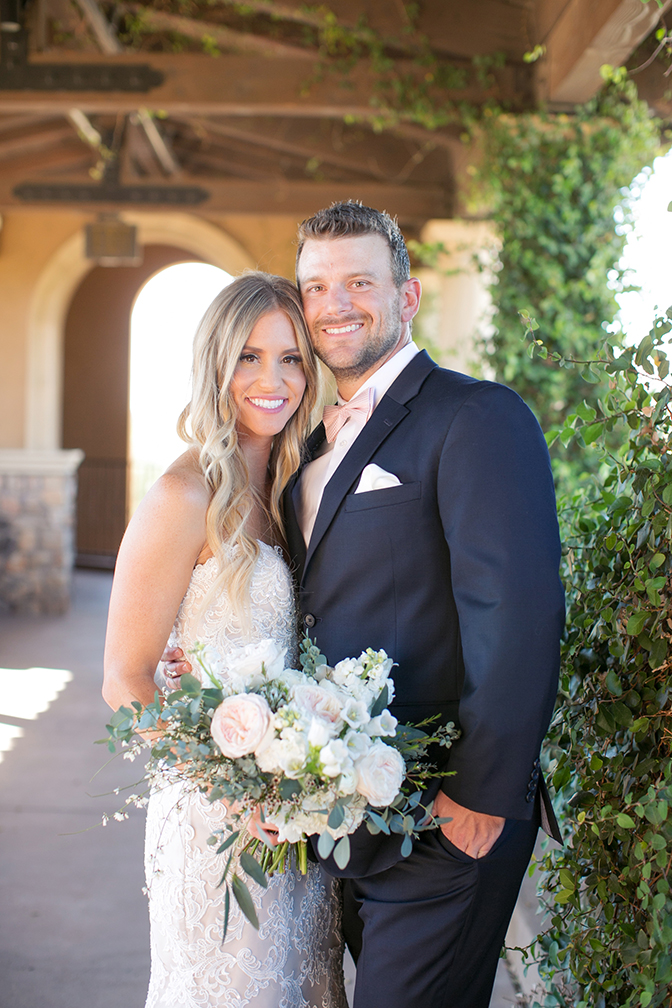 Bride in lace and groom in a navy suit with pink bow tie