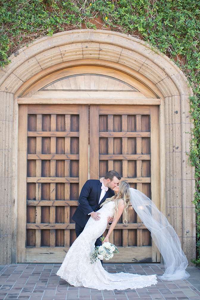 Groom dips his bride for a dramatic kiss