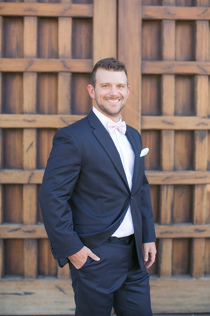 Groom in navy blue with a pale pink tie